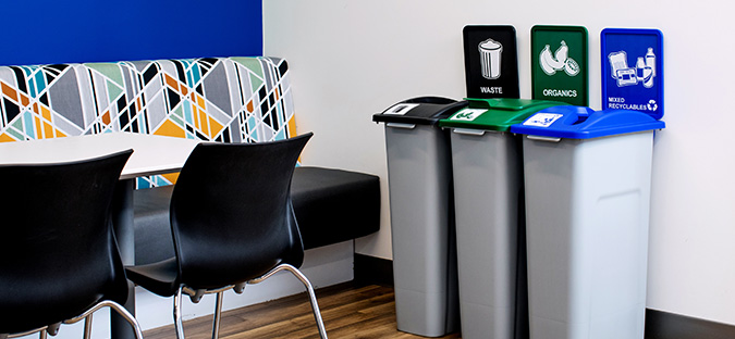 Busch Systems Waste Watcher Series waste recycling and organics containers in an office lunch room